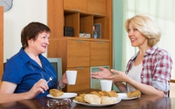 two mature female friends drinking tea and gossiping at table
